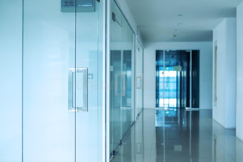 现代办公室内部,蓝色定了调子,在门把的选择聚焦 免版税库存照片