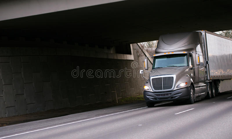 现代半灰色卡车在州际公路的桥梁下 库存照片