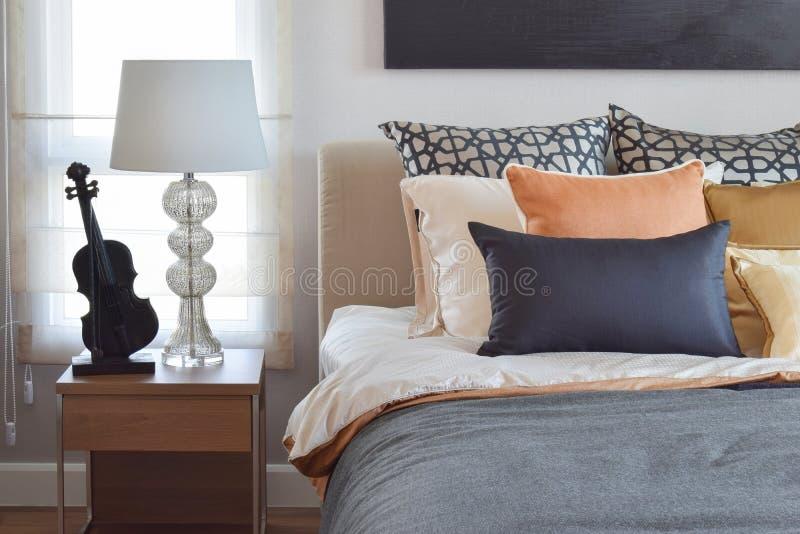 现代卧室内部用桔子和金子在床和台灯上把枕在 免版税库存照片