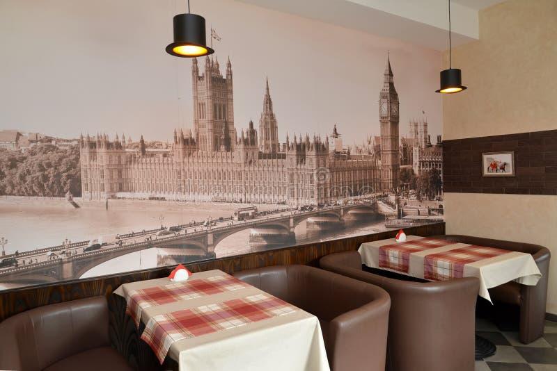 现代咖啡馆内部的片段与威斯敏斯特宫殿的照片的在墙壁上的 免版税库存照片