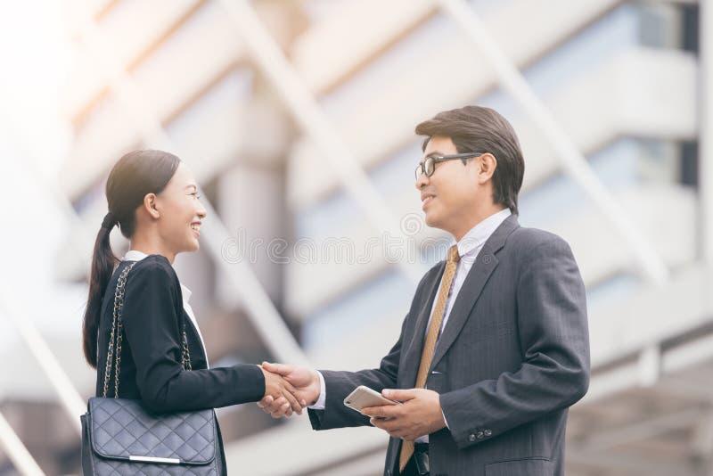 现代商人成交 伙伴握手,站立在他的办公室前面 背景城市晚上街道 免版税图库摄影