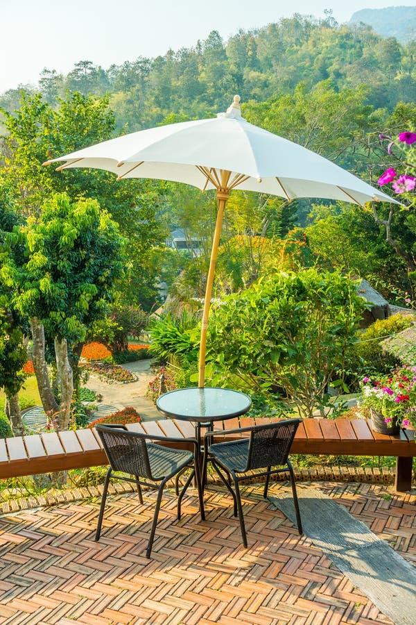 现代圆桌和藤椅与太阳遮蔽伞 免版税图库摄影