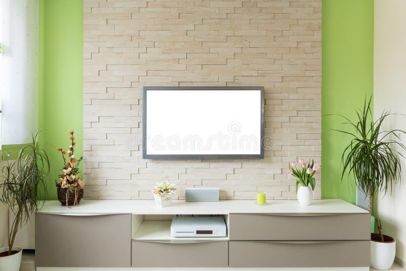 现代客厅内部-电视在有白色屏幕的砖墙登上了 免版税库存照片
