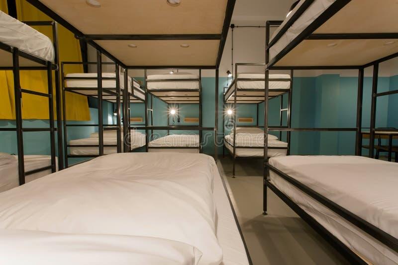 现代家具,在新式的旅舍的床与许多人民的宿舍房间 免版税库存照片