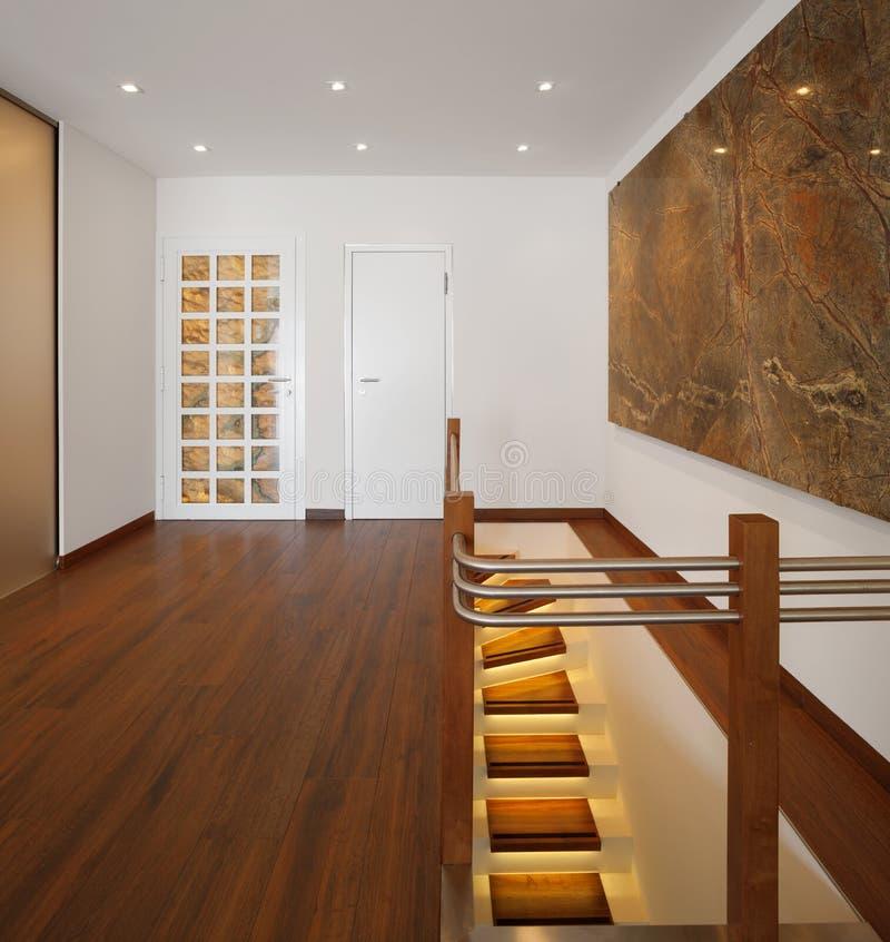 现代房子、词条与木条地板和发亮楼梯 免版税库存图片