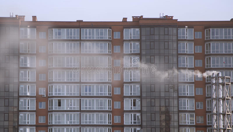 现代房子盖以烟雾 烟危害放射从烟囱的在一个住宅区 免版税库存照片