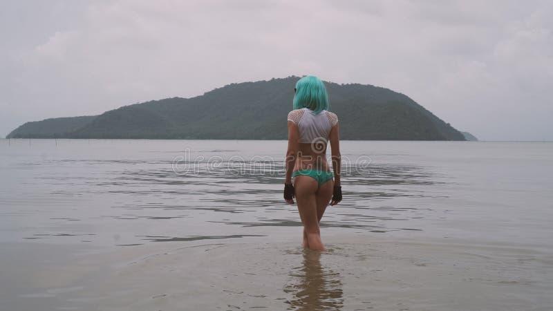 现代未来派样式的性感的妇女与摆在海的蓝色假发 库存图片