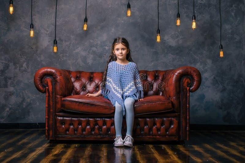 现代沙发的哀伤的小女孩 免版税库存图片