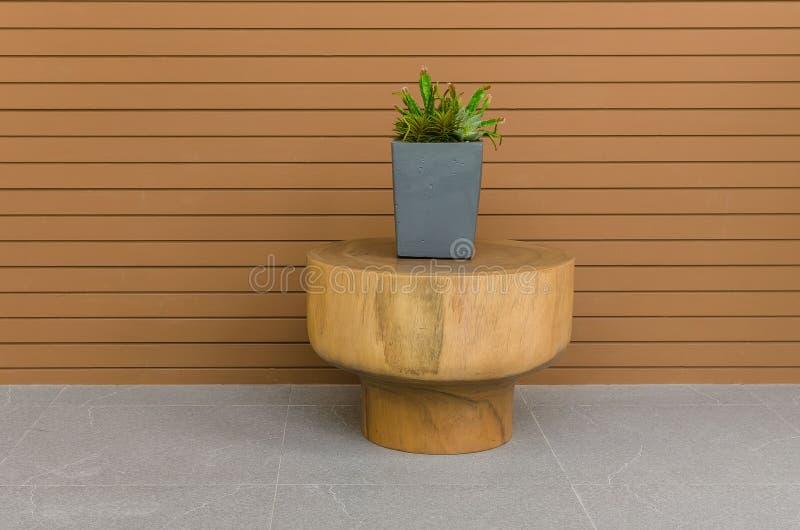 现代灰色罐的植物在与木盘区的圆材桌上 免版税库存图片
