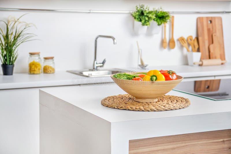 现代白色厨房内部有归纳的烹调的加热器在桌上的菜 图库摄影