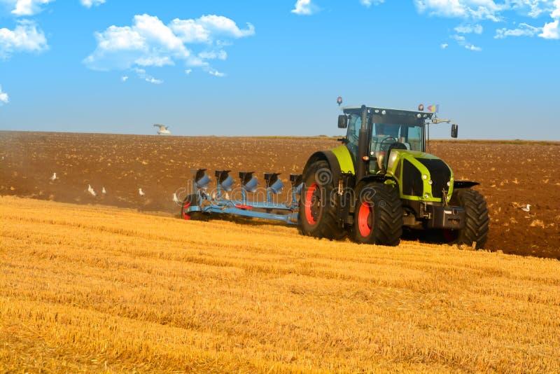 现代种田与在被犁的领域的拖拉机 免版税库存照片