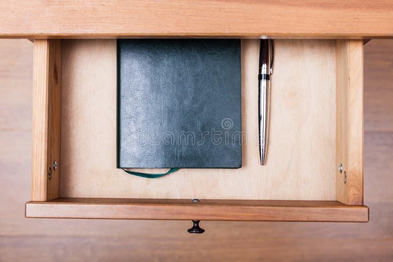 现代笔和笔记本在开放抽屉 免版税库存图片
