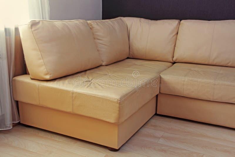 现代米黄壁角皮革沙发在客厅 库存图片