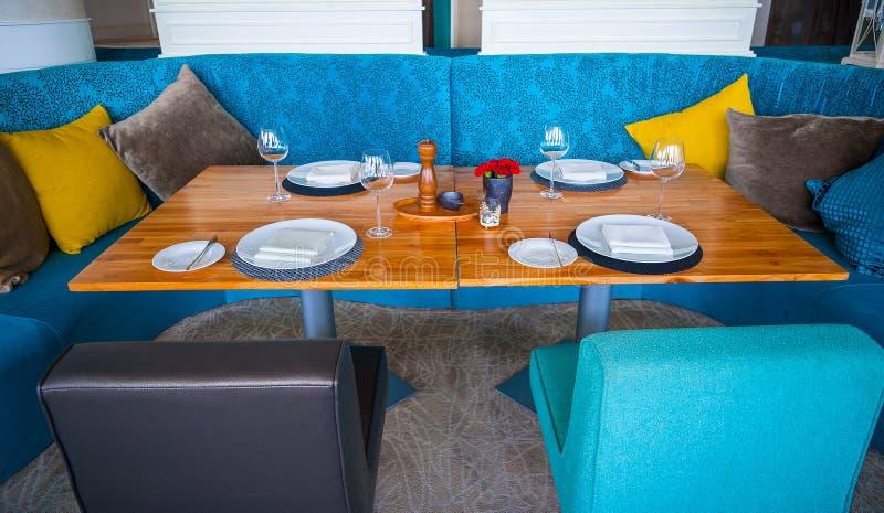现代蓝色餐厅,那里是椅子,并且桌设定了与花梢项目 免版税库存照片