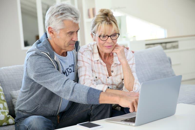 现代资深夫妇在家使用膝上型计算机 免版税库存照片