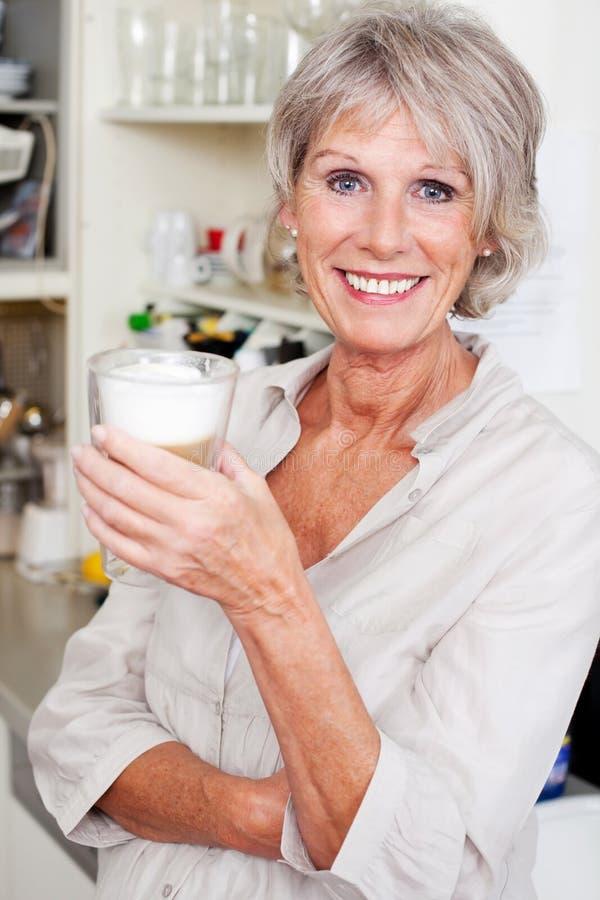 现代资深妇女在她的厨房里 免版税库存图片