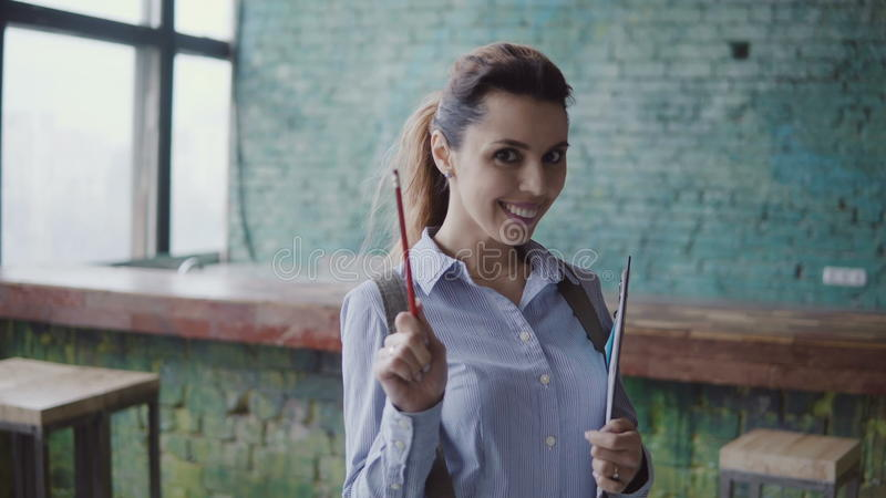 现代coworking的空间的年轻白种人妇女 美丽的女性画象拿着本文,与铅笔的点 免版税库存图片