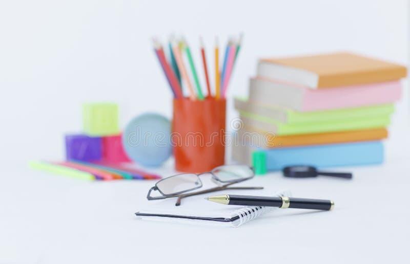 玻璃、笔和笔记本在学校用品背景  与拷贝空间的照片 图库摄影