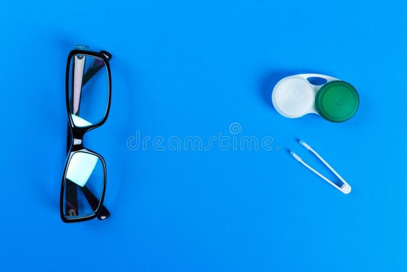 玻璃、隐形眼镜在容器和镊子在蓝色背景 库存照片
