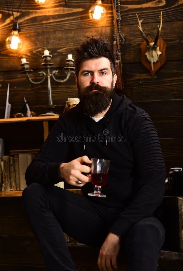 玻璃一百一波兰兹罗提 有胡子的人拿着杯被仔细考虑的酒热的季节性饮料 舒适温暖大气喝的人 图库摄影