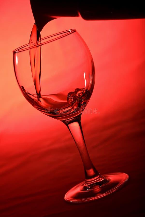 玻璃倾吐的酒 免版税库存照片