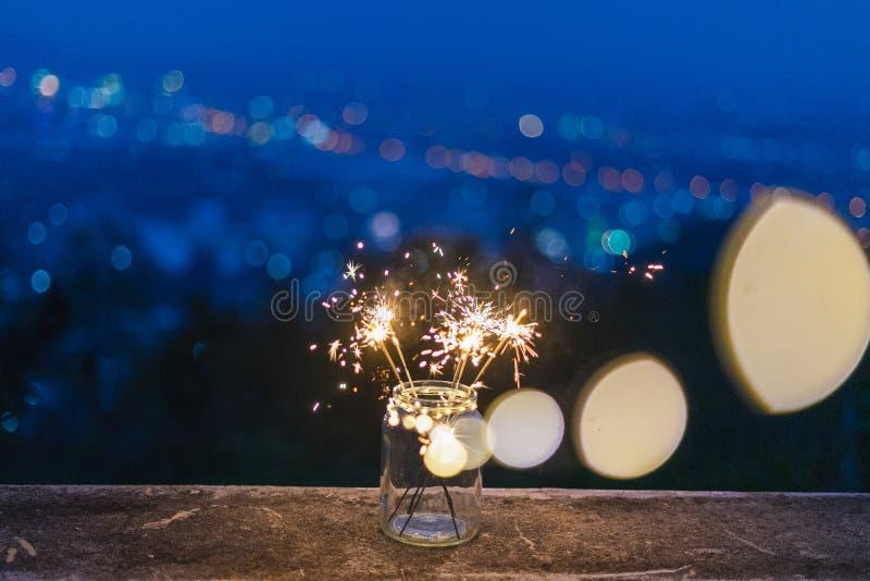 玻璃十二在地板上,与在边的五颜六色的烟花在暮色期间,bokeh背景假日 库存图片