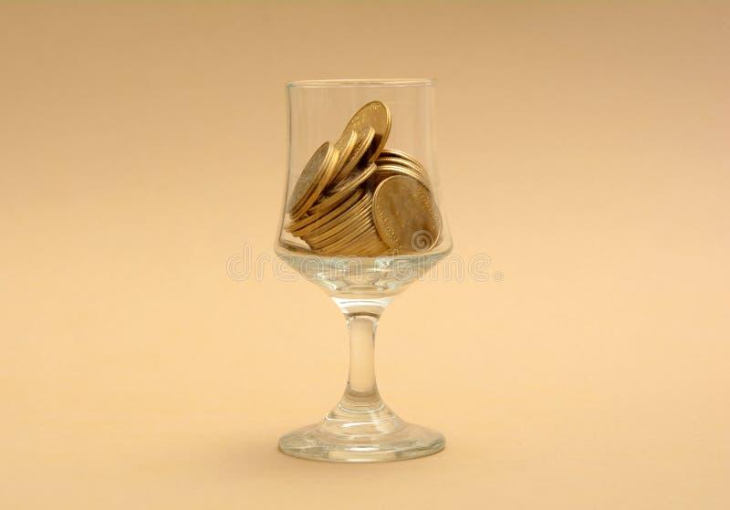 玻璃半满与金黄硬币-财务概念 图库摄影