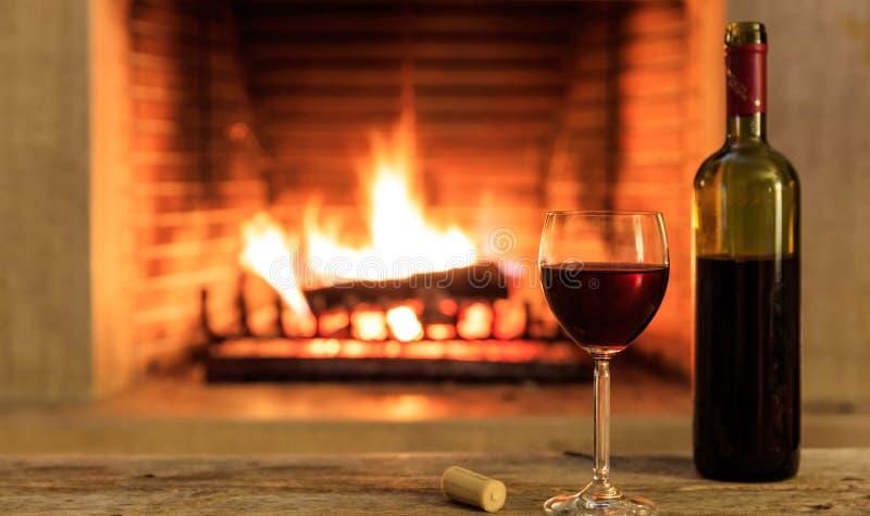 玻璃和一个瓶在灼烧的壁炉背景的红葡萄酒 库存图片