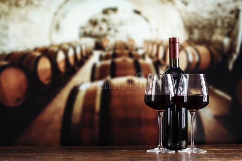玻璃和一个瓶酒在地窖里 库存图片