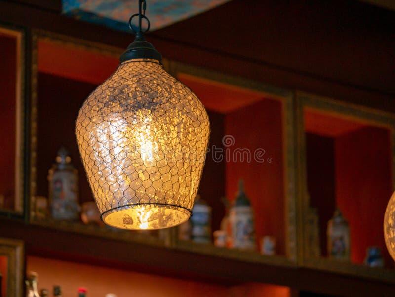 玻璃和导线在一个垂悬的电灯泡的灯盖子在黑暗的酒吧 图库摄影
