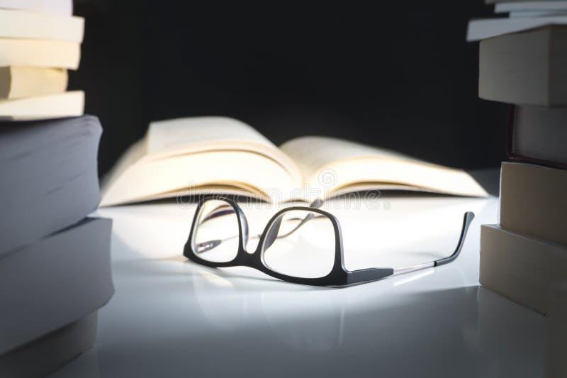 玻璃和开放书在文学围拢的桌上 图库摄影