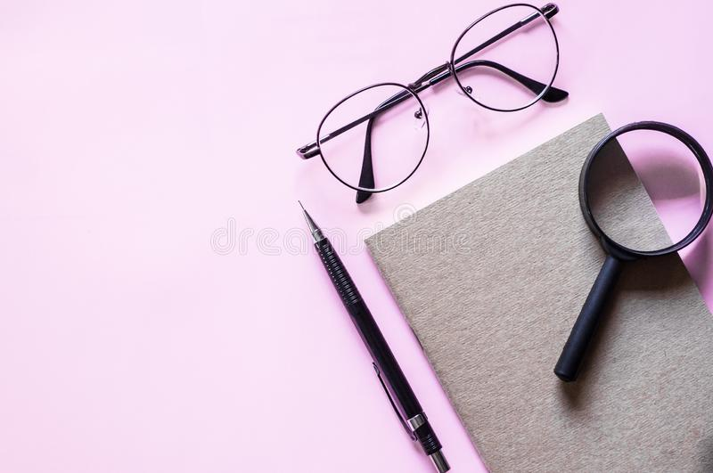 玻璃和放大镜在黑名册最小的样式布局事假空白文本的 免版税库存照片