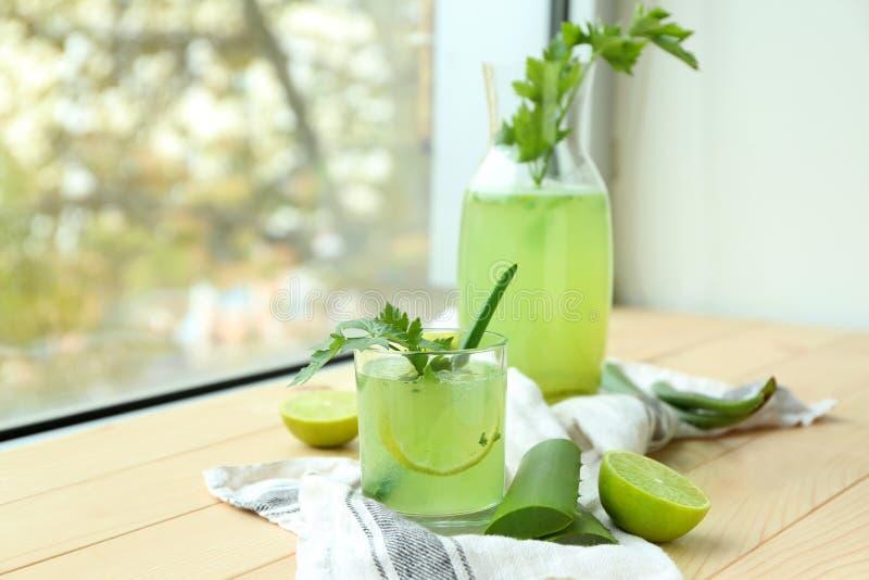 玻璃和水罐芦荟在木窗台的维拉鸡尾酒 库存图片