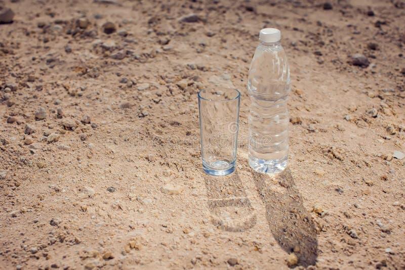 玻璃和瓶水在沙漠 渴,热和天旱概念 免版税库存图片