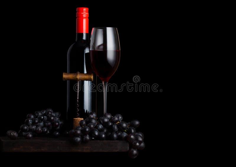 玻璃和瓶红葡萄酒用黑暗的葡萄和葡萄酒螺旋式前进开启者和黄柏在木板在黑背景 空间为 库存图片