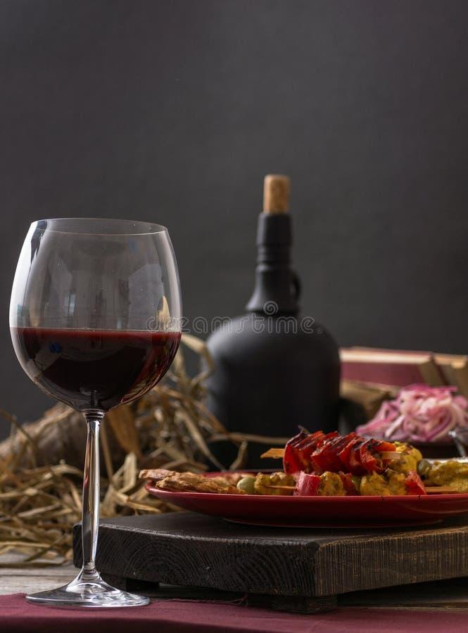玻璃和瓶酒、乳酪和熏火腿在木背景 仍然1寿命 免版税库存照片
