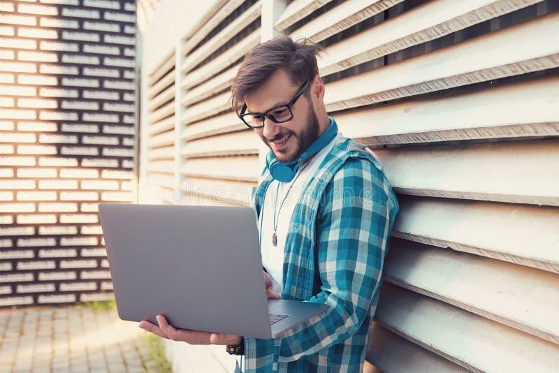 玻璃和耳机的现代行家人使用站立户外在街道上的膝上型计算机 免版税库存图片