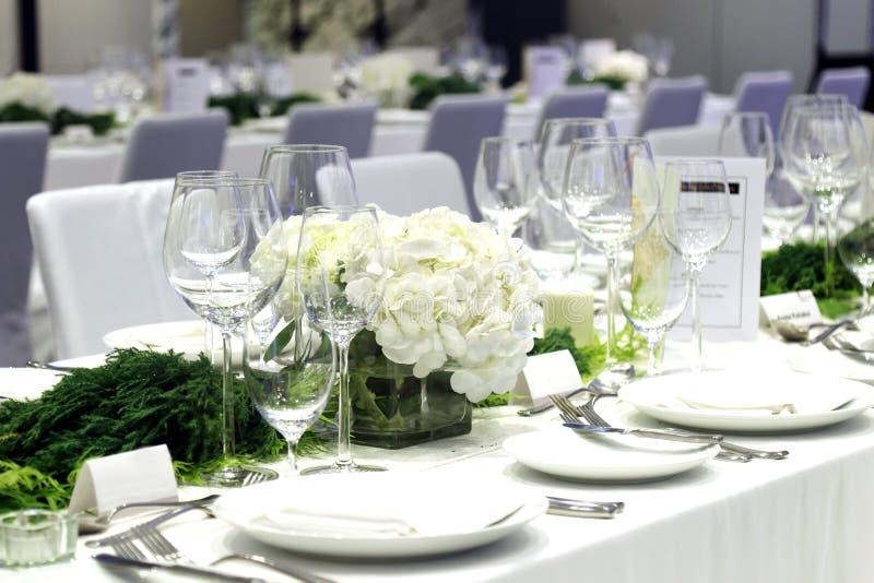 玻璃器皿和板材、酒杯、宴会桌、会议室、研讨会或者党 免版税库存图片