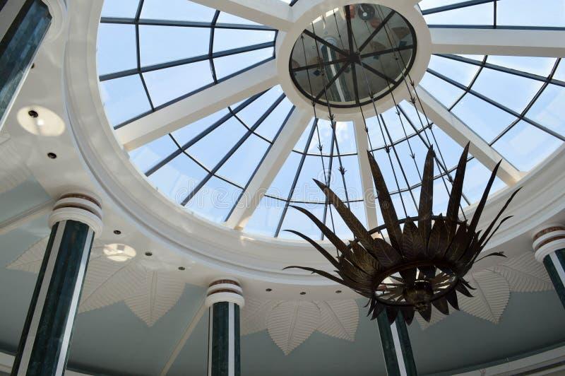 玻璃圆顶、一个大厦的屋顶与许多窗口的和美丽的专栏,与反对蓝天的一盏枝形吊灯 库存照片
