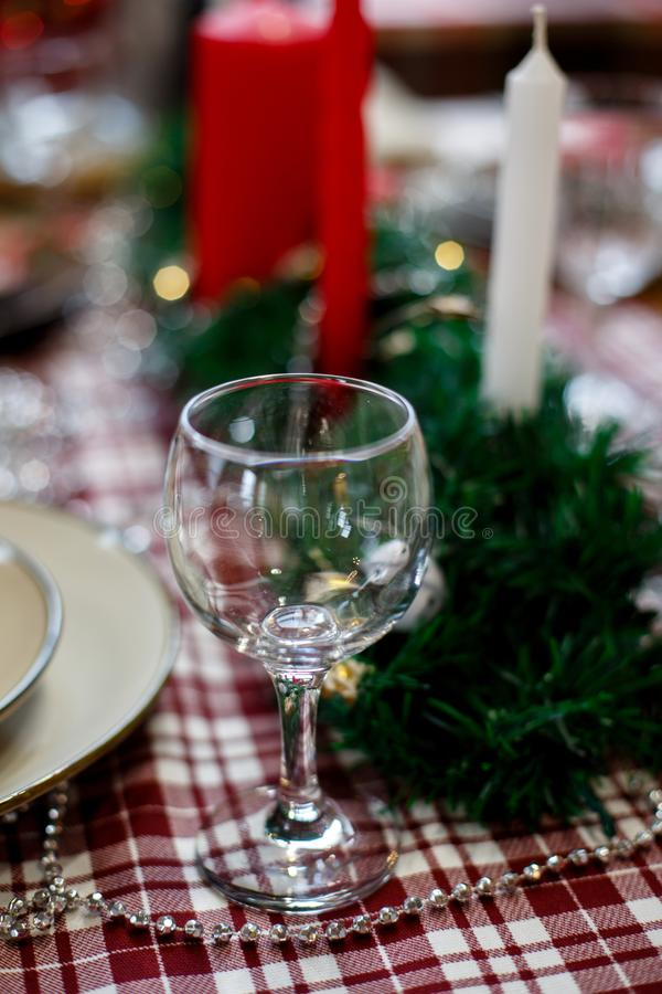 玻璃在用蜡烛和闪亮金属片装饰的圣诞节桌上 库存图片