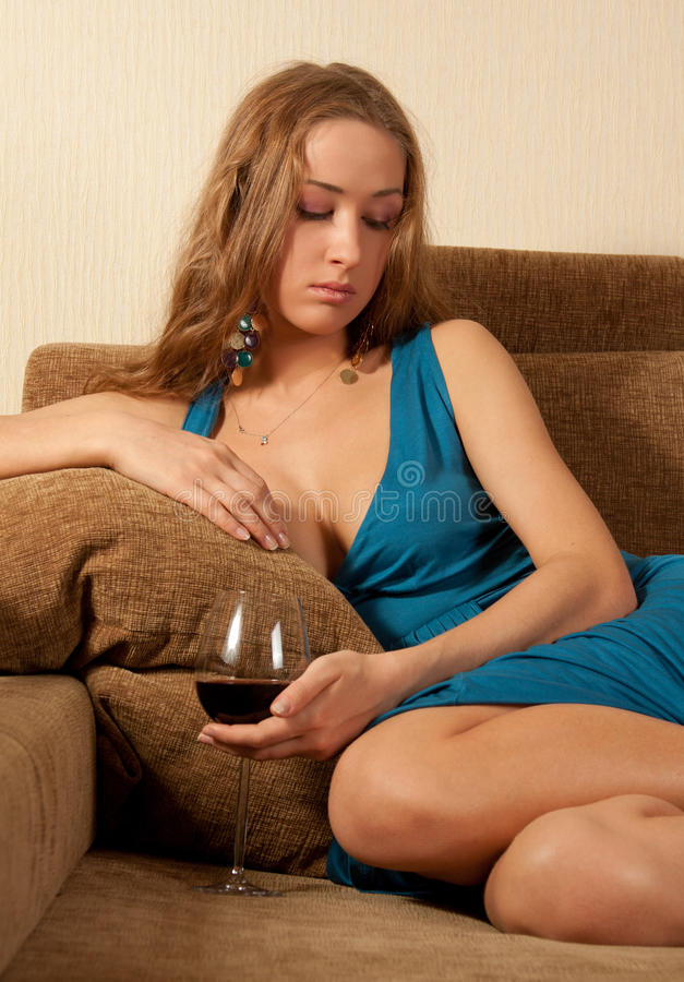玻璃坐沙发酒妇女年轻人 库存图片