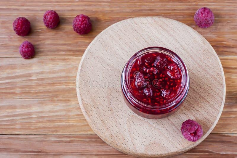 玻璃小茶碟用山莓果酱用新鲜的莓在木背景关闭  r 免版税库存照片