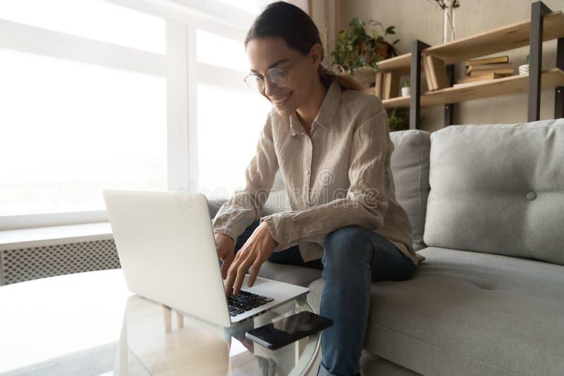 玻璃工作的妇女键入在计算机上的感到满意 库存照片