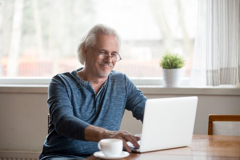 玻璃工作的微笑的老人在膝上型计算机在家 免版税库存图片