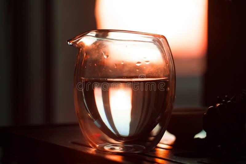 玻璃投手在木桌上的热的茶在美好的日落背景与太阳光芒的 免版税库存图片
