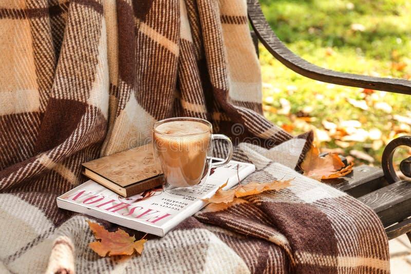 玻璃杯子与温暖的格子花呢披肩、书和杂志的热的咖啡在长木凳在秋天公园 免版税库存图片