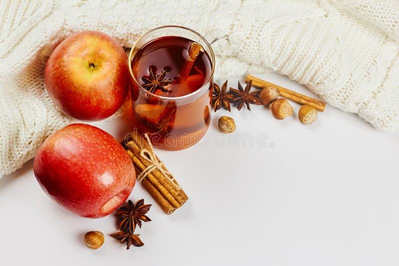 玻璃杯子与苹果切片、桂香和茴香的热的辣发球区域在与拷贝空间的白色被编织的背景 免版税库存图片