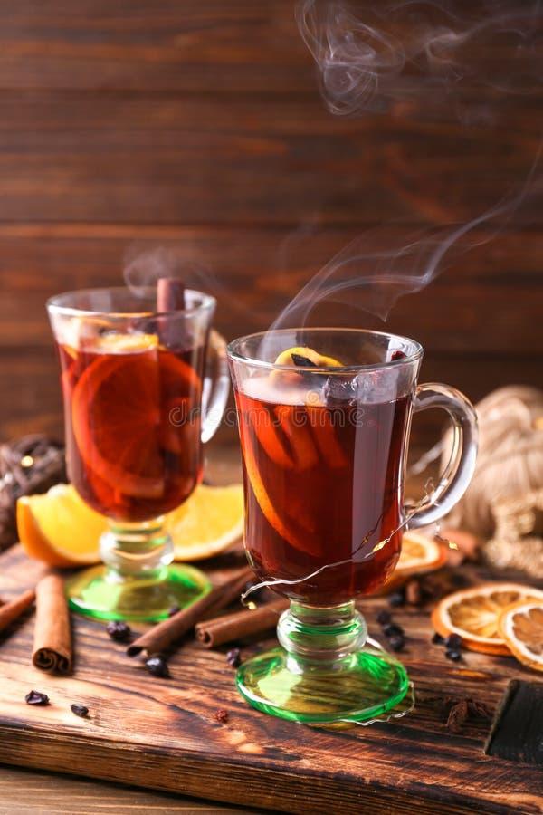 玻璃杯子在木板的可口热的加香料的热葡萄酒 免版税库存照片