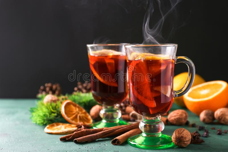 玻璃杯子在颜色表上的可口热的加香料的热葡萄酒 库存图片