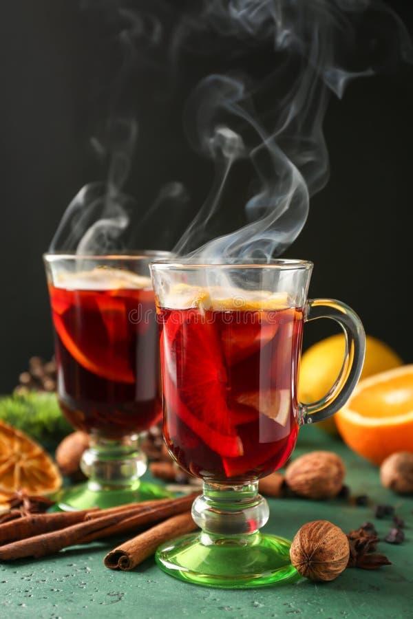 玻璃杯子在颜色表上的可口热的加香料的热葡萄酒 库存照片